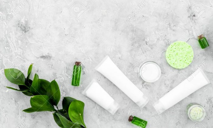 Organic skin care products. Cream, lotion, tonic. oil near green leaves on grey background top view.